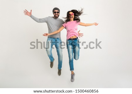 hipster stylish couple jumping isolated on white background, pretty smiling emotional woman and man dressed in jeans, active and positive, having fun together #1500460856