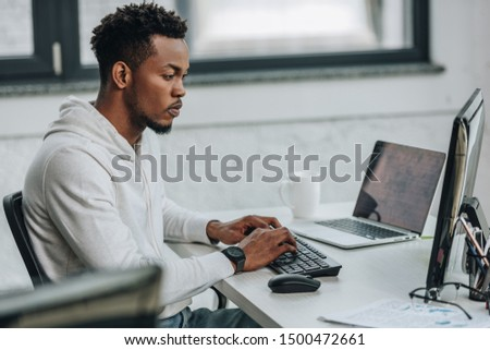 selective focus of attentive african american programmer working on computer in office #1500472661