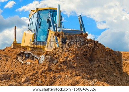 Crawler bulldozer - excavator with clipping path on a background with blue sky and clouds. work on construction site or sand pit #1500496526