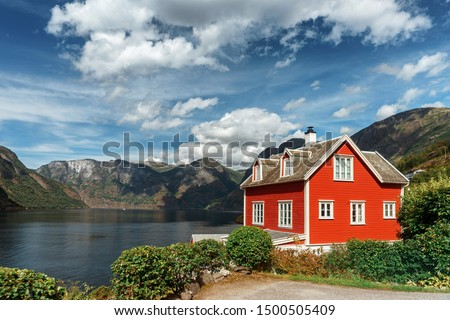 Typical Norwegian red house in the background of a picturesque fjord. Beautiful Norwegian landscape with a red house and atmospheric sky. #1500505409