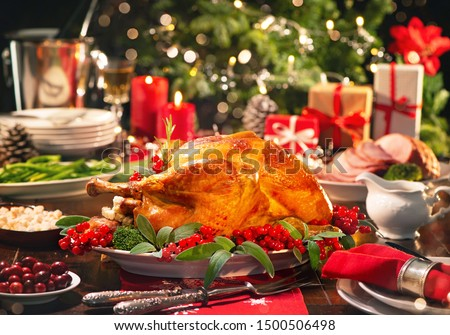 Christmas turkey dinner. Baked turkey garnished with red berries and sage leaves in front of Christmas tree and burning candles #1500506498