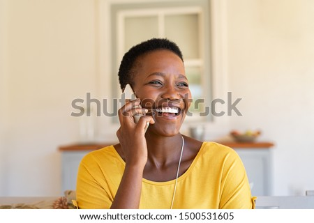 Smiling african american woman talking on the phone. Mature black woman in conversation using mobile phone while laughing. Young cheerful lady having fun during a funny conversation call. Royalty-Free Stock Photo #1500531605