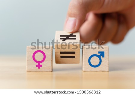 Concepts of gender equality. Hand flip wooden cube with symbol unequal change to equal sign  #1500566312