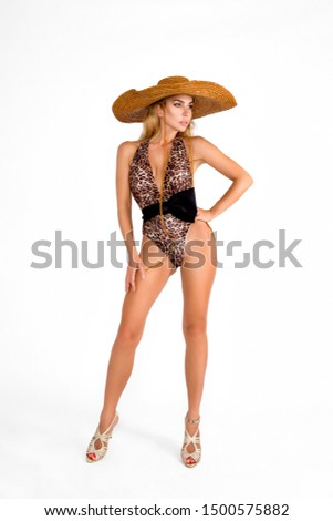 fashion photo of beautiful tanned woman with blond hair in elegant leopard print bikini and big hat on a white background in studio - Picture
