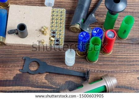 reloading process shotgun shells with special reload equipment. Powder, bullets, fraction, shells, buckshot on the wooden background #1500603905