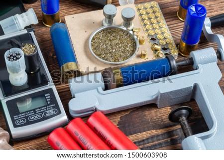 reloading process shotgun shells with special reload equipment. Powder, bullets, fraction, shells, buckshot on the wooden background #1500603908