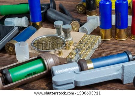 reloading process shotgun shells with special reload equipment. Powder, bullets, fraction, shells, buckshot on the wooden background #1500603911