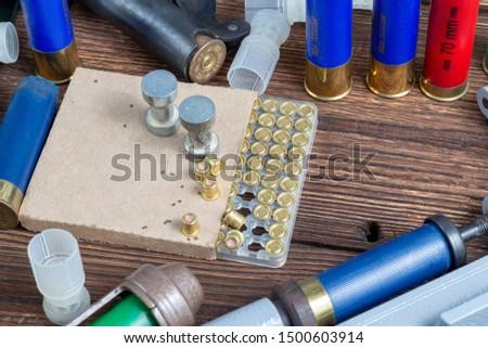 reloading process shotgun shells with special reload equipment. Powder, bullets, fraction, shells, buckshot on the wooden background #1500603914