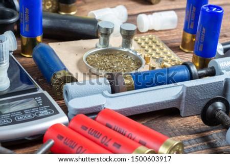 reloading process shotgun shells with special reload equipment. Powder, bullets, fraction, shells, buckshot on the wooden background #1500603917