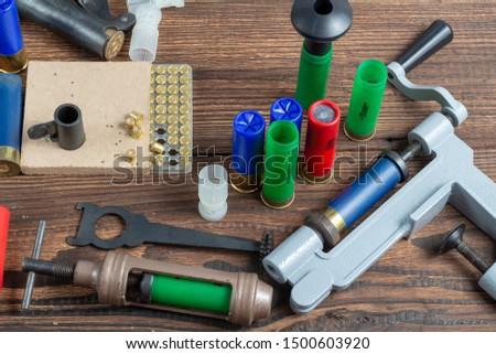 reloading process shotgun shells with special reload equipment. Powder, bullets, fraction, shells, buckshot on the wooden background #1500603920