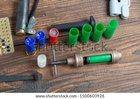 reloading process shotgun shells with special reload equipment. Powder, bullets, fraction, shells, buckshot on the wooden background #1500603926