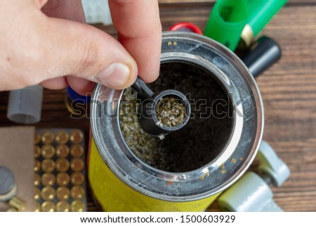reloading process shotgun shells with special reload equipment. Powder, bullets, fraction, shells, buckshot on the wooden background #1500603929