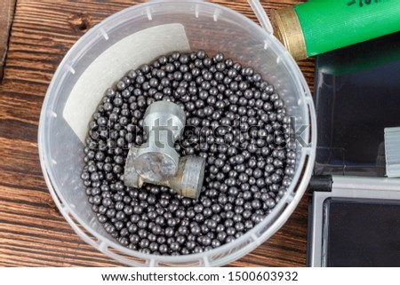reloading process shotgun shells with special reload equipment. Powder, bullets, fraction, shells, buckshot on the wooden background #1500603932