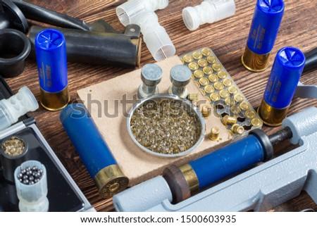 reloading process shotgun shells with special reload equipment. Powder, bullets, fraction, shells, buckshot on the wooden background #1500603935