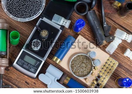 reloading process shotgun shells with special reload equipment. Powder, bullets, fraction, shells, buckshot on the wooden background #1500603938