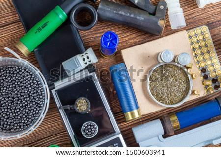 reloading process shotgun shells with special reload equipment. Powder, bullets, fraction, shells, buckshot on the wooden background #1500603941