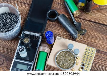 reloading process shotgun shells with special reload equipment. Powder, bullets, fraction, shells, buckshot on the wooden background #1500603944
