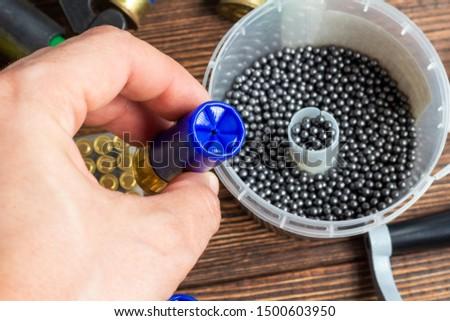 reloading process shotgun shells with special reload equipment. Powder, bullets, fraction, shells, buckshot on the wooden background #1500603950