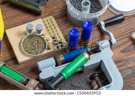 reloading process shotgun shells with special reload equipment. Powder, bullets, fraction, shells, buckshot on the wooden background #1500603953