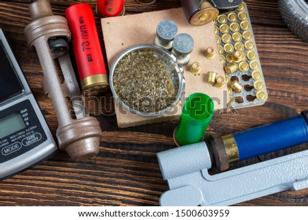 reloading process shotgun shells with special reload equipment. Powder, bullets, fraction, shells, buckshot on the wooden background #1500603959