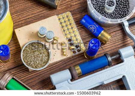 reloading process shotgun shells with special reload equipment. Powder, bullets, fraction, shells, buckshot on the wooden background #1500603962
