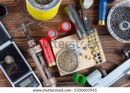 reloading process shotgun shells with special reload equipment. Powder, bullets, fraction, shells, buckshot on the wooden background #1500603965