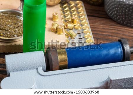 reloading process shotgun shells with special reload equipment. Powder, bullets, fraction, shells, buckshot on the wooden background #1500603968