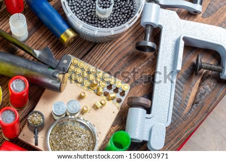 reloading process shotgun shells with special reload equipment. Powder, bullets, fraction, shells, buckshot on the wooden background #1500603971
