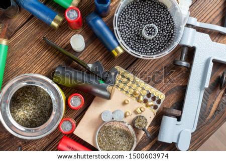 reloading process shotgun shells with special reload equipment. Powder, bullets, fraction, shells, buckshot on the wooden background #1500603974