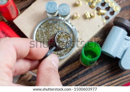 reloading process shotgun shells with special reload equipment. Powder, bullets, fraction, shells, buckshot on the wooden background #1500603977
