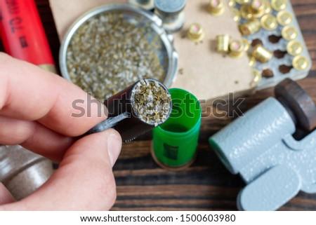 reloading process shotgun shells with special reload equipment. Powder, bullets, fraction, shells, buckshot on the wooden background #1500603980