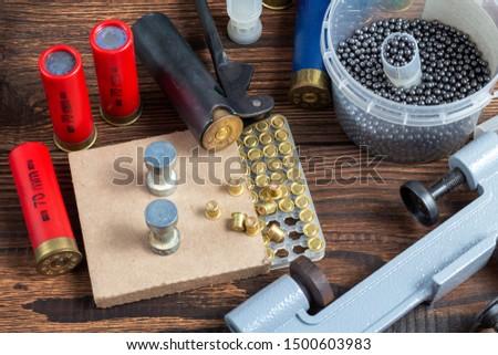 reloading process shotgun shells with special reload equipment. Powder, bullets, fraction, shells, buckshot on the wooden background #1500603983