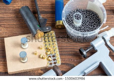 reloading process shotgun shells with special reload equipment. Powder, bullets, fraction, shells, buckshot on the wooden background #1500603986