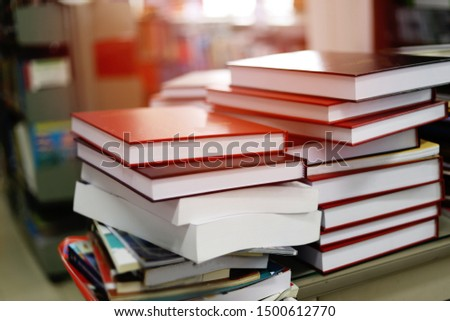 Blurred background of pile of books in the study room of high school, college, or university campus. Education or academic concept picture of literary works on a desk in the teacher's research room