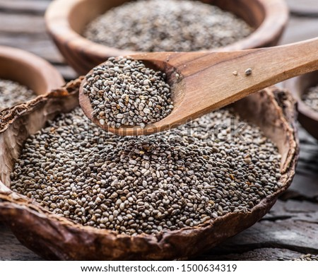 Chia seeds in wooden spoon over organic dish with chia seeds on old wooden table. #1500634319