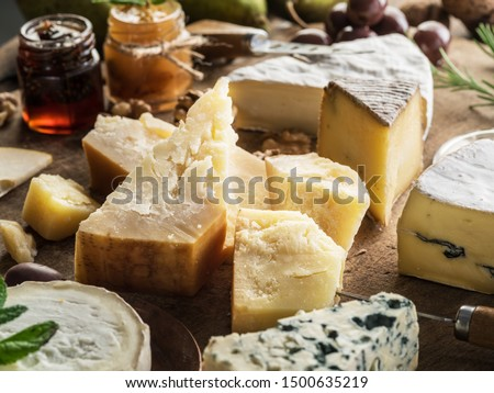 Piece of Parmesan cheese and assortment of different cheeses at the background. #1500635219