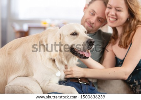 Young happy married couple nice girl and young man in casual clothes talking with his kind obedient dog in the living room of his cozy country house #1500636239