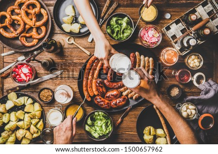 Flat-lay of Oktoberfest dinner table with grilled meat sausages, pretzel pastry, potatoes, cucumber salad, sauces, beers and peoples hands clinking glasses over dark wooden background, top view #1500657962