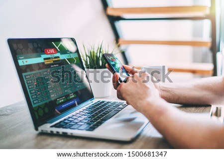 Close up cropped shot of male hands making bets using gambling mobile application on his phone. Man watching football match online broadcast on his laptop waiting for winning results. Royalty-Free Stock Photo #1500681347