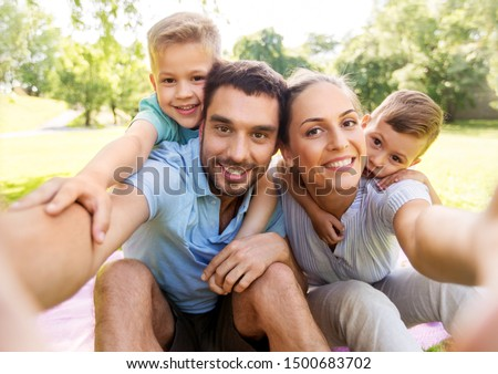 family, leisure and technology concept - happy mother, father and two little sons having picnic and taking selfie at summer park #1500683702