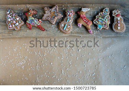 Christmas baking on the wooden board on the table. Decorated gingerbreads with hundreds and thousands. Copy space. #1500723785