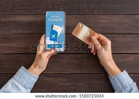 Woman buying airline tickets online with app on smartphone and credit card, dark wooden background with copy space #1500725024