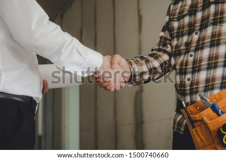 construction worker team contractor shaking hands with engineer after finishing up business meeting to start up project contract in construction site building, teamwork, partnership, industry concept #1500740660