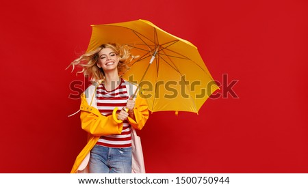 young happy emotional cheerful girl laughing and jumping with yellow umbrella   on colored red background #1500750944