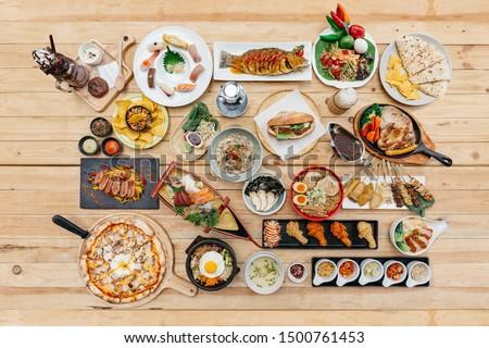 Top view of International Foods on wooden table include Sushi, Sashimi, Nachos, Spaghetti, Naan, Sandwich, Noodle, Steak, Ramen. Yakitori, Pizza, Bibimbap, Fried Chicken Wings, Brownie Frappe. #1500761453