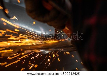 Worker cutting metal part using hand Angle Grinder Machine. Freeze motion sparks , close-up. #1500912425