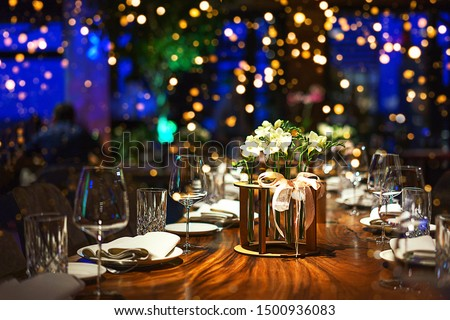 Classic Blue color of the Year 2020.Holiday party blurred background made from decorated table with bouquet of flowers and colorful lights bokeh. Selective focus. Christmas dinner, table setting. #1500936083