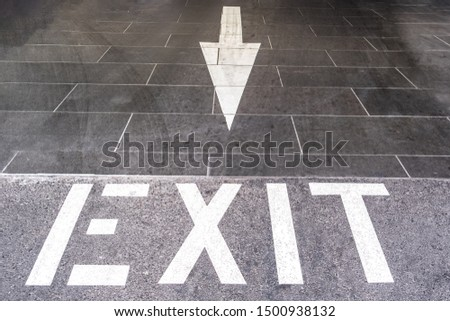 Exit text with arrow painted on the floor of underground parking exit #1500938132