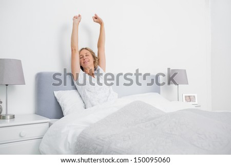 Blonde woman stretching her arms in bed in the morning in bedroom at home #150095060