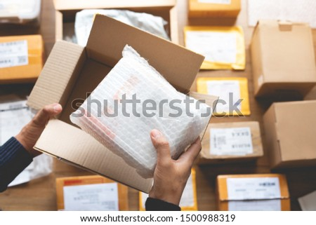 Online shopping concepts with male hand packing some product to brown box on another packet for shipping to customer.Ecommerce,delivery and logistic network.Business retail market Royalty-Free Stock Photo #1500988319